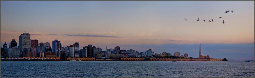 26 de Março - Porto Alegre (RS) - O centro da cidade junto ao Guaíba, a linha de armazéns históricos do Cais Mauá e à direita a alta chaminé da Usina do Gasômetro, ambos ícones