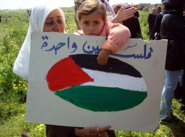 30 de Março - 1976 — Os primeiros protestos do Dia da Terra são realizados em Israel-Palestina - Criança exibe cartaz com a bandeira da Palestina, no Dia da Terra. Beit Hanoun, Faix