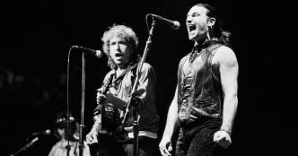 10 de Maio - 1960 - Bono, cantor da banda U2 com Bob Dylan cantando 'Blowing in the Wind'.