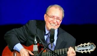 10 de Junho - João Gilberto - cantor, violonista e compositor brasileiro - rindo no palco com o violão.