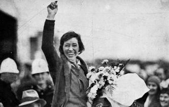 1 de Julho - Amy Johnson, aviadora norte-americana, acenando para o público.