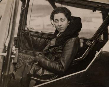 1 de Julho - Amy Johnson, aviadora norte-americana, dentro do avião, séria.