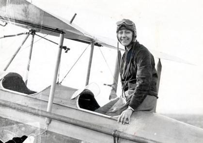 1 de Julho - Amy Johnson, aviadora norte-americana, no avião, sorrindo.