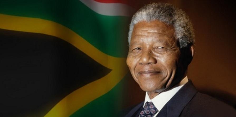 18 de Julho - Nelson Mandela - 1918 – 99 Anos em 2017 - Acontecimentos do Dia - Foto 8 - Com a bandeira da África do Sul ao fundo.