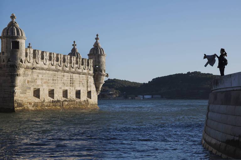 Turistas tira foto da Torre de Belém, às margens do rio Tejo, na capital Lisboa